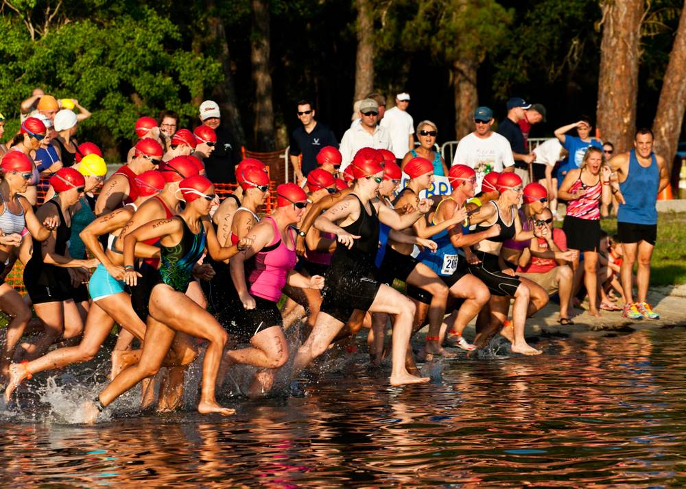 Group of triathlon competitors rush to the water to begin the swiming portion.