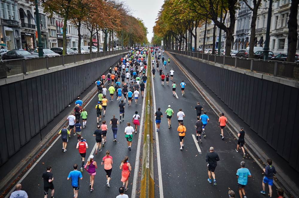 Marathon runners exiting a road tunnel viewed from the top street level.