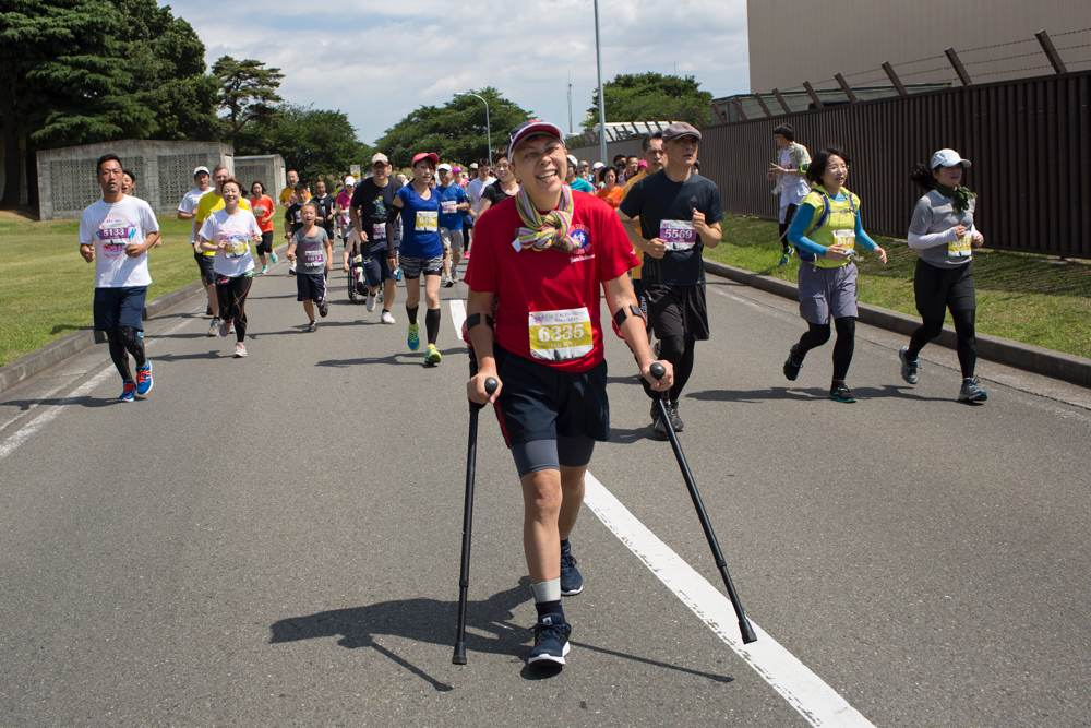 Older woman walks on marathon competition with the help of crutches.