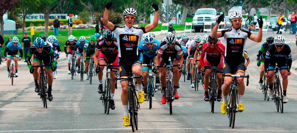 A cyclist celebrates his approach to the finish line with extended arms in front of the other competitors.