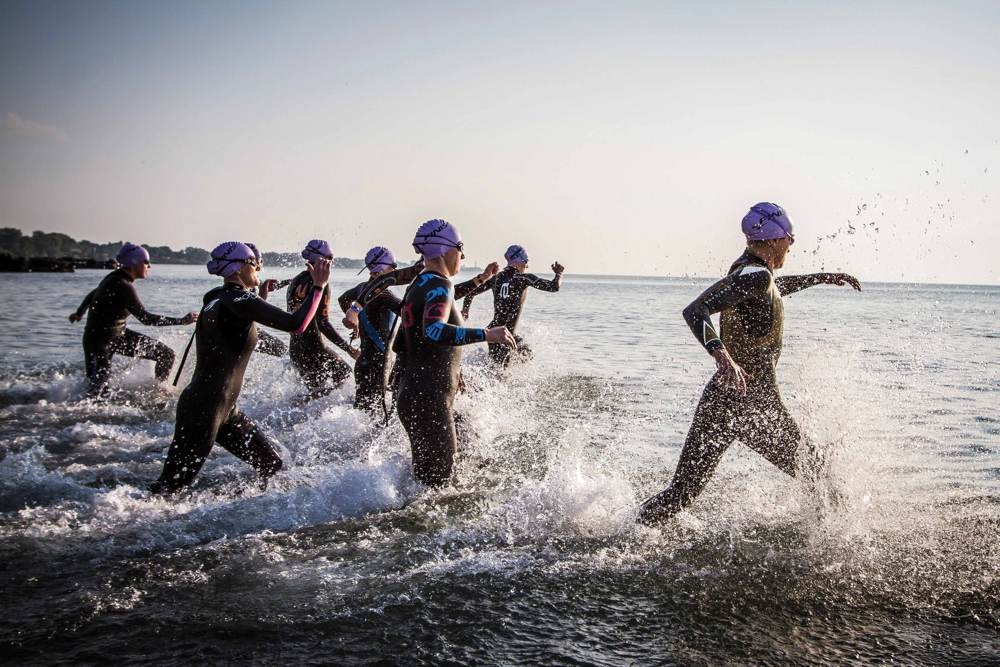 Group of swimmers in wetsuits run to the water to begin the swimming race.