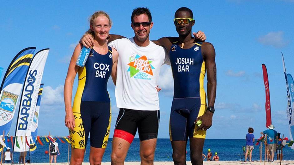 Three triathlon competitors pose together for the camera on a beach.