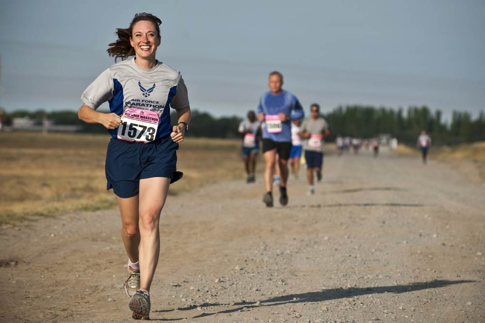 Woman running on a dirt road ahead of the competition pack smiling for the camera.